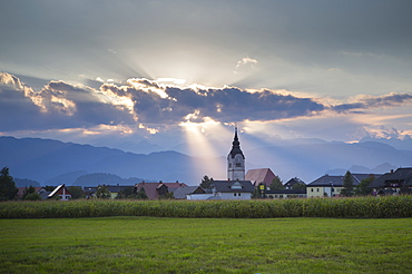 Beautiful scene with sunbeams shining above church in village of Lesce near Bled, Upper Carniola, Slovenia
