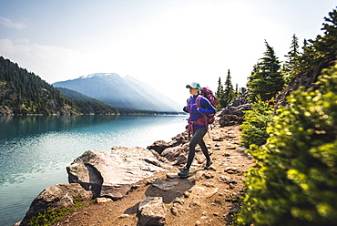 Woman hiking along shore of Lake Garibaldi, British Columbia, Canada
