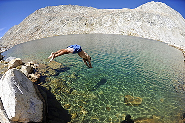 Man diving into La Salle Lake while hiking on a two-week trek of the Sierra High Route in the John Muir Wilderness in California. The 200-mile route roughly parallels the popular John Muir Trail through the Sierra Nevada Range of California from Kings Canyon National Park to Yosemite National Park.