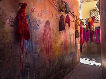 Colorful fabrics hanging in narrow alley decorated with handprints, Marrakesh, Morocco