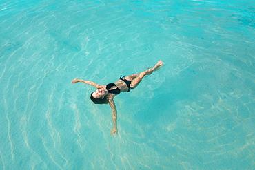 Woman in bikini floating on water, Tambon Ko Tarutao, Chnag Wat Krabi, Thailand
