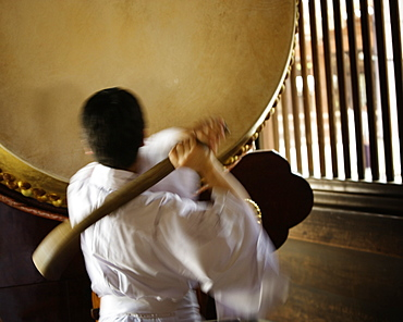 A man ready to strike a taiko (a great or fat drum). Tokyo, Japan.