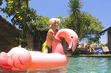 Side view of blonde boy with pink flamingo inflatable ring in swimming pool