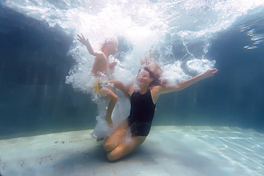 Underwater view of mother and son swimming in swimming pool