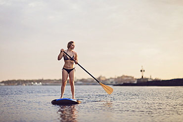 A woman paddles a paddleboard across the harbor at sunset in Portland, Maine