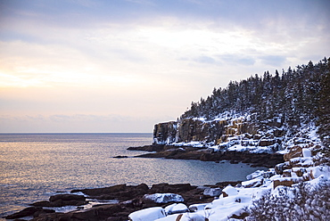 Scenic view of Otter Cliffs covered with snow at sunrise, Acadia National Park, Maine, USA