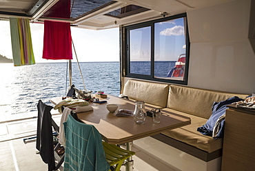 View of table, seats and chairs on deck of catamaran