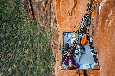 View from above of single young woman lying on portaledge while rock climbing Moonlight Buttress, Zion National Park, Utah, USA