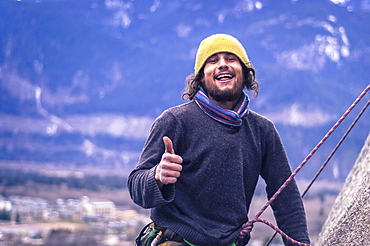 Happy rock climber with thumbs up, knit hat and beard, Squamish, British Columbia, Canada