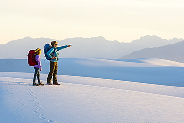 Side view of woman and girl hiking in White Sands National Monument, Alamogordo, New Mexico, USA