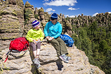 Mother and daughter resting and eating while hiking in Heart of Rocks, Chiricahua National Monument, Willcox, Arizona, USA
