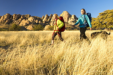 Mother and daughter hiking through dry grass below Sheepshead in Cochise Stronghold, Tombstone, Arizona, USA