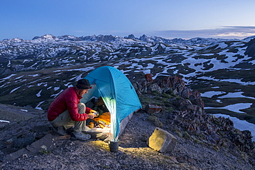 A man camping with a tent above Stony Pass near the Grenadiers and the Weminuche Wilderness, Silverton, Colorado, USA