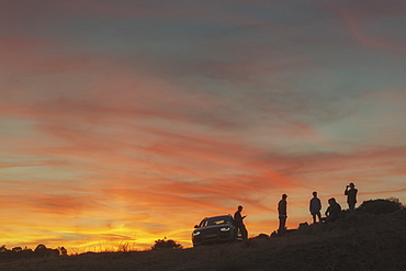 Silhouette of group of friends near car at sunset in natural setting