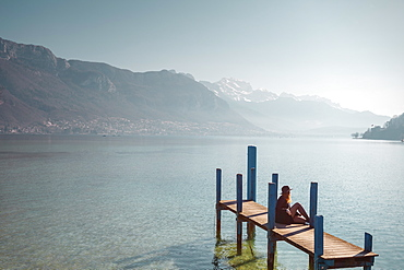 Woman sitting on jetty on lakeshore under clear sky with mountains in background, Annecy, Haute-Savoie,