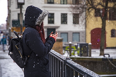 Side view shot of woman wearing hooded jacket and backpack taking picture with smartphone on bridge, Copenhagen, Denmark