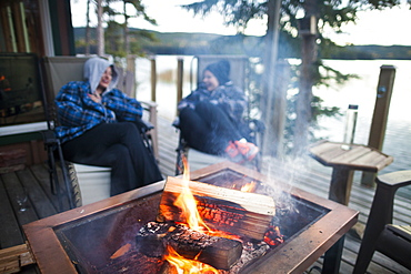 Two laughing women sitting around burning campfire