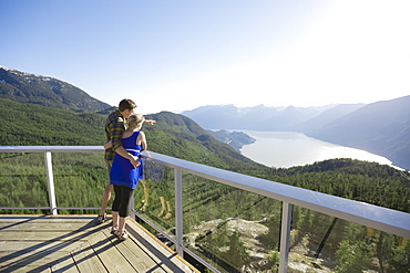 Rear view of couple standing at observation point in natural setting under clear sky, Vancouver, British Columbia, Canada