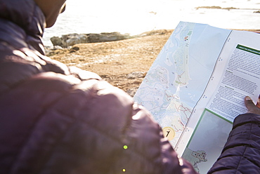 Over the shoulder view of single woman checking map, Kittery, Maine, USA