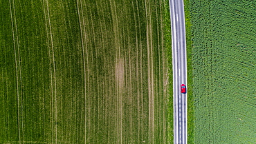 Aerial view of car driving down road surrounded by fields, Genolier, Vaud Canton, Switzerland