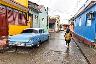 Rear view of female tourist walking on street by vintage car in Baracoa, Guantanamo Province, Cuba - 857-95328