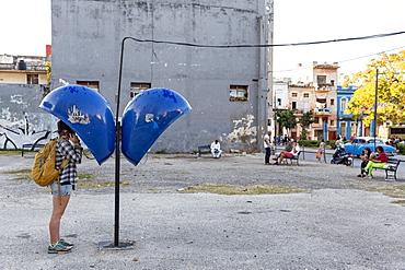 Side view of female tourist using payphone, Havana, Cuba