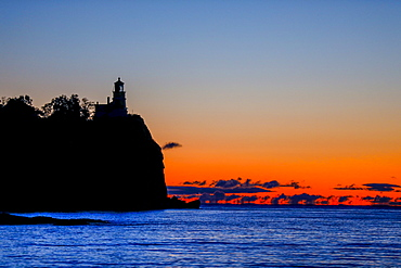 Silhouette of lighthouse on coastal cliff at sunset, Two Harbors, Minnesota, USA