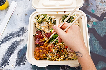 View from above of person eating traditional Hawaiian poke meal with chopsticks, Kona, Hawaii, USA