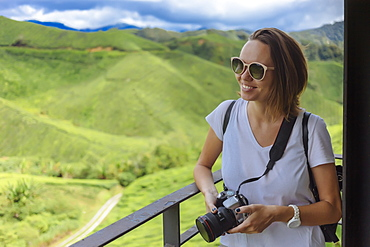 Waist up shot of smiling female tourist with sunglasses and camera at tea plantation, Cameron Highlands, Malaysia