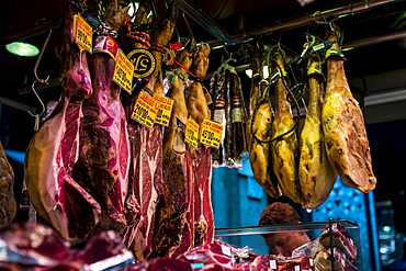 Various meat hanging in La Boqueria market in Barcelona, Spain