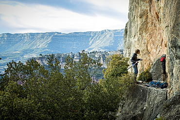 Distant view of single adventurous male rock climber preparing stick clip at cliff, Siurana, Catalonia, Spain