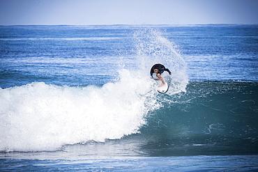 Full length shot of single boy in wetsuit surfing in sea