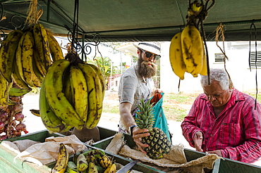 Man with beard buying fruit from market stall, Vinales, Pinar del Rio Province, Cuba