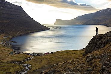 Distant view of man standing on seashore, Faroe Islands, Denmark