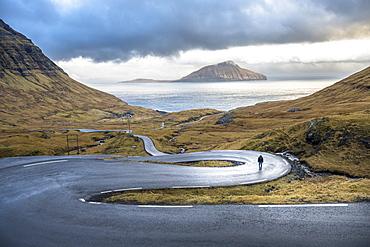Distant view of man walking on winding road on seashore, Faroe Islands, Denmark