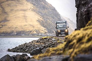 Front view of 4x4 car driving along coastline, Faroe Islands, Denmark