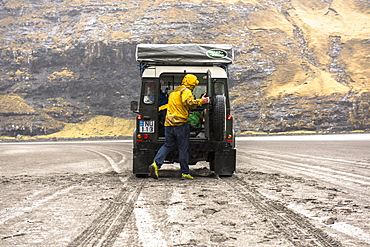 Rear view of man looking in trunk of 4x4 car in natural setting, Faroe Islands, Denmark