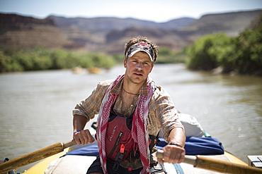Raft guide man rowing and looking at camera during rafting trip, Desolation/Gray Canyon section, Utah, USA