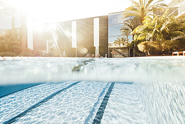 Backlit half in/half out picture of swimming pool in front of hotel and palm trees, Mallorca, Balearic Islands, Spain