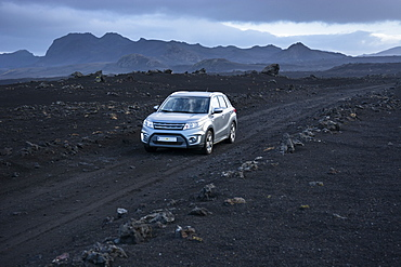 Silver-colored 4x4 SUV driving along dirt road in volcanic landscape, Sprengisandsleid, Iceland