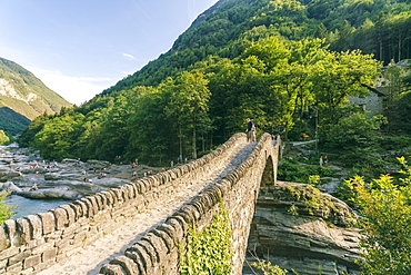Mountainscape with stoned bridge across river in Alps in summer, Verzasca, Ticino, Switzerland