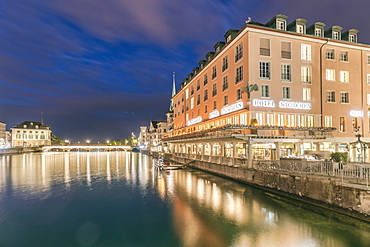 Illuminated hotel building by river Limmat at night, Zurich, Switzerland