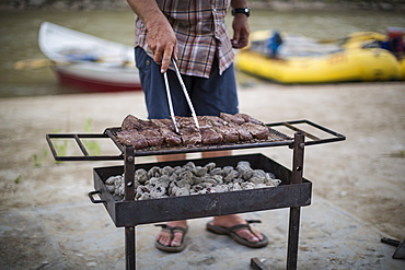 Raft guide with cooking steaks on grill in outdoor kitchen during Green River rafting trip, Desolation/Gray Canyon, Utah, USA