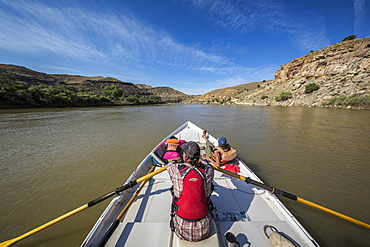 Man and two women sailing across calm Green River in Desolation Canyon, Utah, USA