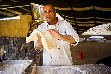Chef throwing bread dough of shrak (markook) to make it very thin before cooking on hot saj (or domed iron griddle), Wadi Rum Village, Aqaba Governorate, Jordan