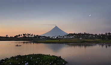 Majestic scenery with Mayon Volcano and man in canoe on lake at dusk, Legazpi City, Albay Province, Philippines