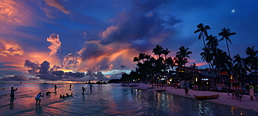 View of beach with silhouettes of tourists and palm trees at sunset, Boracay, Aklan, Philippines