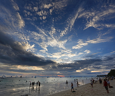 View of tourists on beach under moody sky at sunset, Boracay, Aklan, Philippines