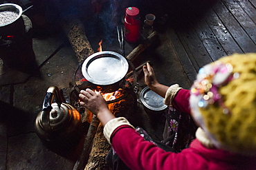 Arms of woman sitting in front of indoor campfire and warming hands, Myanmar, Shan, Myanmar
