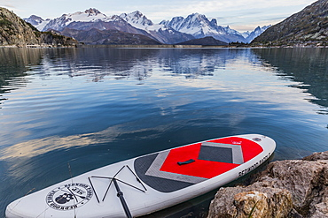 Paddle board near rocky shore on lake in front of mountains, Emosson Dam, Wallis, Switzerland